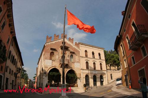 """Il palazzo della Ragione, l'antico tribunale di epoca scaligera. Al centro della piazza l'""""antenna"""" da cui sventolava il gonfalone di Venezia, oggi sostituito dalla bandiera arancione del Touring"""